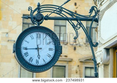image of a street clock on a stone wall