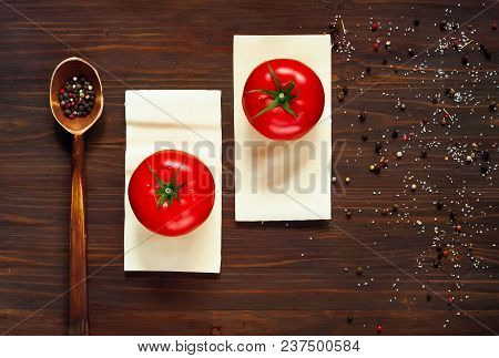 Wooden Spoon With Spices And Red Tomatoes Lie On The Plates Of Dough For Lasagna On A Dark Backgroun