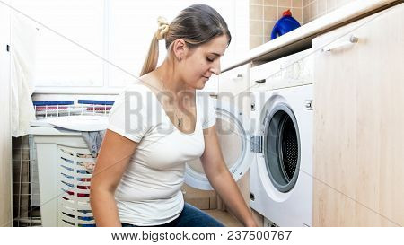 Portrait Of Smiling Housewife Sitting On Floor At Laundry Room