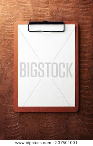 An brown clipboard on a rough wooden desk, with regular white blank paper.