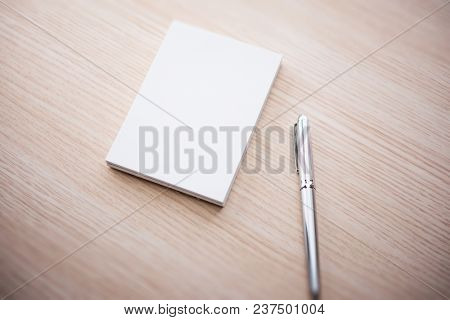 A blank memo pad and a silver pen, on a light colored wood table.  poster