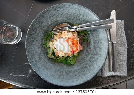 Russian salad with crab leg and poached egg in stoneware plate shot from above