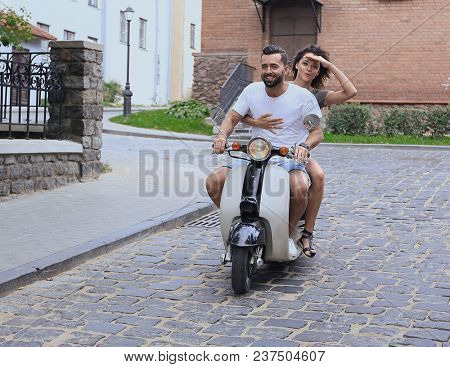 Young couple riding motor scooter in city