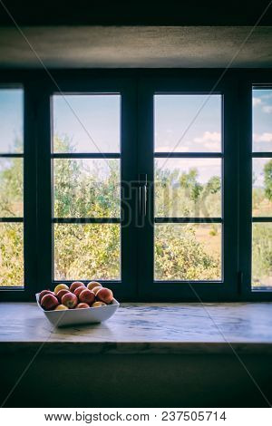 A bowl with assorted fruits near a large window with natural light