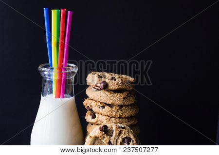 Horizontal Low Key Image Of A Glass Milk Bottle With Milk And Coloured Straws With A Stack Of Chocol
