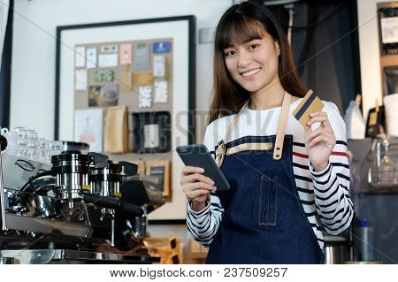 Young Asian Woman Barista Using Smartphone And Holding Credit Card At Cafe Counter, Food And Drink B