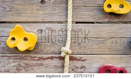 Closeup Photo Of Rope And Rocks For Climbing On Wooden Wall