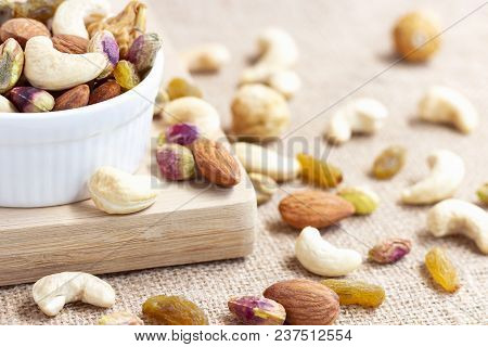 Dried Fruits And Variety Of Nuts Into A Bowl On Wooden Background, Such As Figs, Almonds, Raisins, C