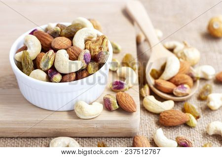 Dried Fruits And Variety Of Nuts Into A Bowl, A Wooden Spoon On The Sackcloth Background, Such As Fi
