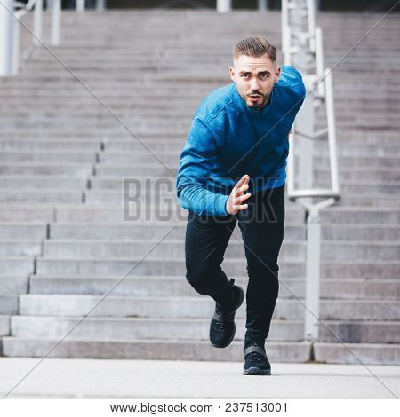 Handsome sportsman in athletic clothes, running fast. Sprinter. Fit lifestyle.