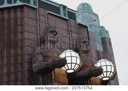 HELSINKI, FINLAND - JANUARY 27, 2018: Statues of Lantern Carriers at the Helsinki central railway station. The station building was designed by Eliel Saarinen and inaugurated in 1919
