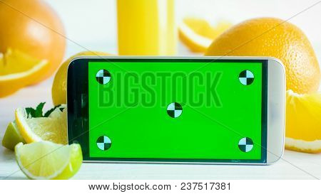 Closeup Photo Of Smartphone With Green Chroma Key Screen With Fresh Oranges And Lemons. Perfect For