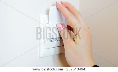Closeup Photo Of Young Woman In Hotel Room Inserting Key Card In Holder