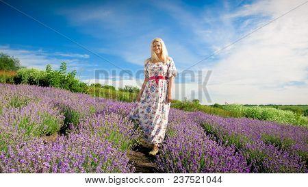 Blonde Woman In Long Dress Standing On Lavender Field