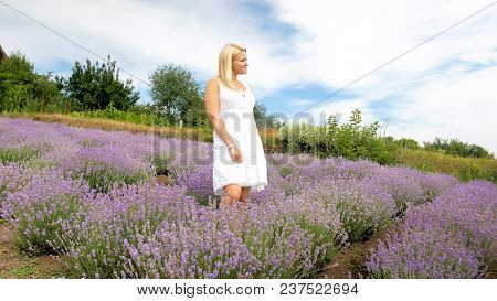Young Woman In Dress Posing In Lavender Field