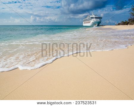 A cruise ship docks in the port of Grand Turk in the Caribbean with white sand beach in the foreground.