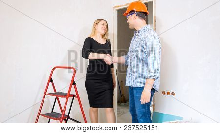 Businesswoman Shaking Hand To Male Contractor In House Under Construction
