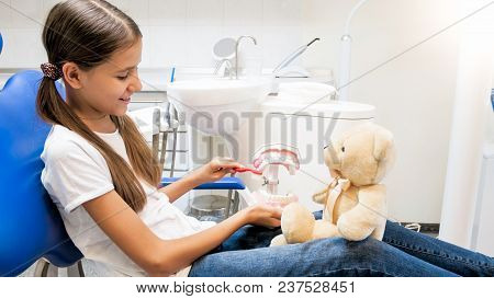 Smiling Girl Sitting In Dentist Chair And Playing With Teddy Bear