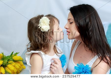 Beautiful Young Mother And Little Daughter In The Same Blue Dresses On The Sofa With A Bouquet Of Fl