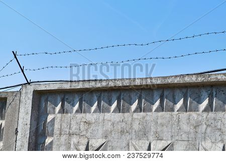 Concrete Fence With Barbed Wire On Blue Sky Background. Barbed Wire Is Fixed On Top With Metal Rods.