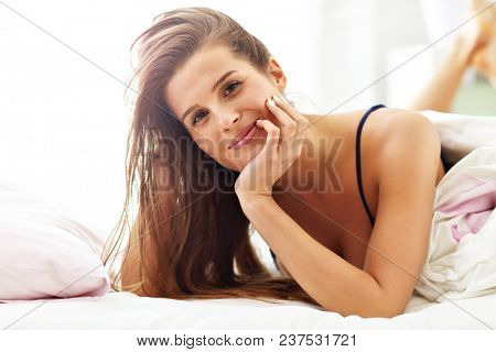 Young woman waking up in bed