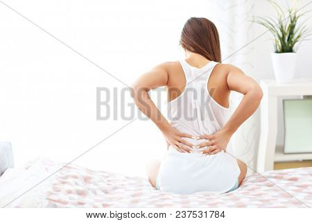 Young woman waking up in bed with backache