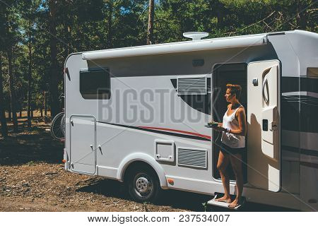 Side View Of A Young Woman Standing Holding A Dish And A Bowl On A Caravan Door Parked On A Forest O