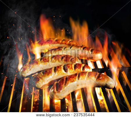 Grilled sausage on the flaming grill with smoke