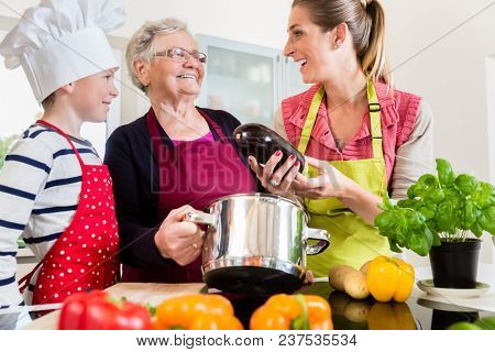 Happy granny, mum and son talking while cooking in kitchen