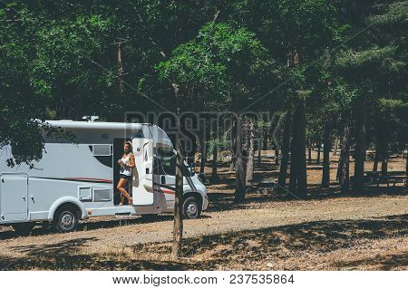 Young Woman Is Relaxing Having A Cup Of Tea Standing On A Caravan Door Parked On A Forest On A Holid