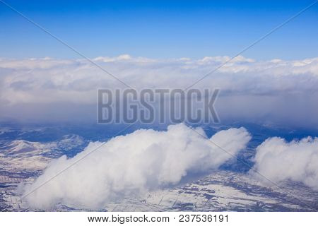 White clouds background hanging on blue sky over snowy mountain. Aerial photo from airplane's window.