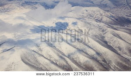 Snowy mountains background and white clouds. Aerial photo from airplane's window.