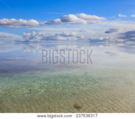 Sandy calm sea, blue sky with few white clouds background. Summer destination for holiday and relaxing. Reflection of clouds on crystal aquamarine transparent sea.
