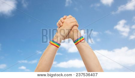 lgbt, same-sex relationships and homosexual concept - close up of male hands wearing gay pride awareness wristbands making winning gesture over blue sky and clouds background