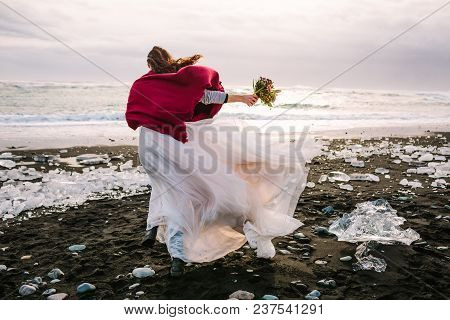 Bride In White Flattering Dress With Burgundi Plaid Walking In Windy Day On Black Sand Beach, Icelan