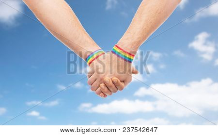 lgbt, same-sex relationships and homosexual concept - close up of male couple wearing gay pride rainbow awareness wristbands holding hands over blue sky and clouds background