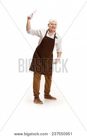 Smiling Happy Butcher Posing With A Knife Isolated On White Studio Background. The Young Caucasian M