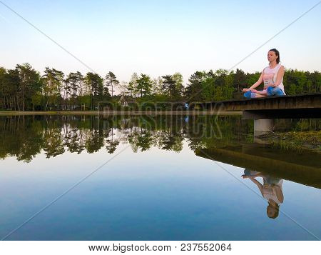 Young woman practices yoga and meditates in the lotus position on the peer of a lake on a sunny evening poster