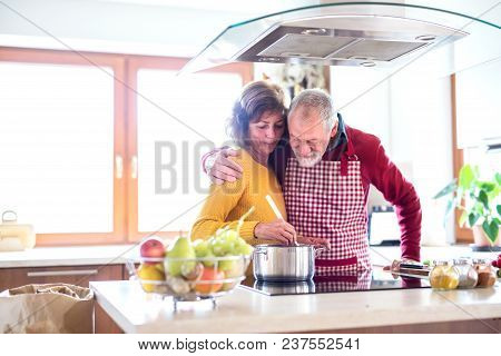 Senior Couple Preparing Food In The Kitchen. An Old Man And Woman Inside The House Cooking.