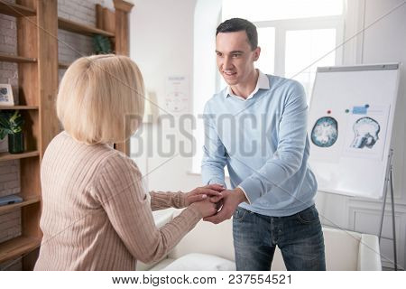 Good Day. Senior Woman And Attractive Man Standing While Greeting Each Other