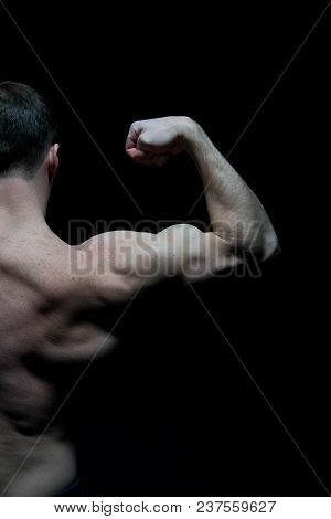 Man Athlete With Half Torso, Back View. Sportsman Flex Arm Muscles. Bodybuilder Show Biceps And Tric