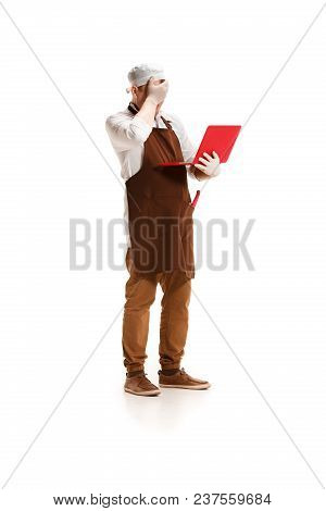 Sorry Saddened Butcher Posing With A Laptop Isolated On White Studio Background. The Young Caucasian
