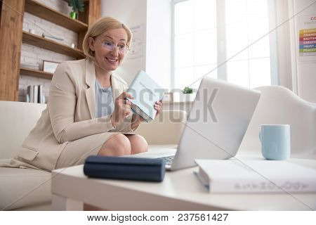 Useful Reading. Gay Mature Businesswoman Looking At Screen While Holding Book