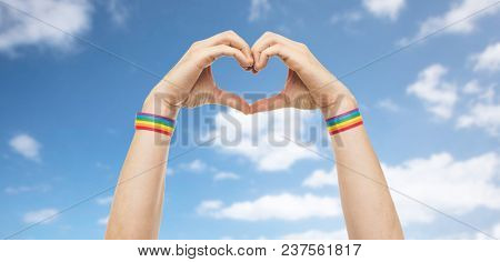 lgbt, same-sex love and homosexual relationships concept - close up of male hands with gay pride rainbow awareness wristbands showing heart gesture over blue sky and clouds background