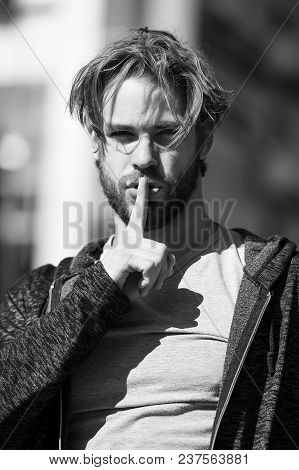 Macho With Hush Finger On Lips, Bearded Face And Blond Hair Haircut In Grey Tshirt On Sunny Day Outd