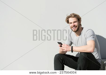 Happy Macho With Smartphone On Sunny Outdoor. Bearded Man Smile With Mobile Phone On Grey Wall. Guy