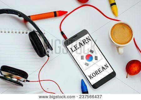 Smartphone With Korean Flag And Headphones. Concept Of Korean Learning Through Audio Courses