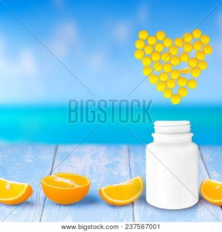 Heart Of Yellow Medicines, Tablets And Capsules For The Treatment Of Heart Diseases On A Wooden Tabl
