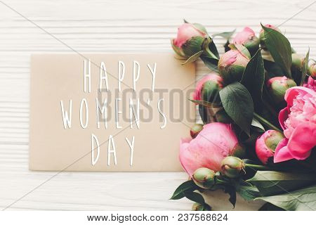 Happy Women's Day Text On Card And Pink Peonies Bouquet On Rustic White Wooden Background In Light,