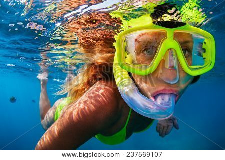 Happy Girl In Snorkeling Mask Dive Underwater With Tropical Fishes In Coral Reef Sea Pool. Travel Li